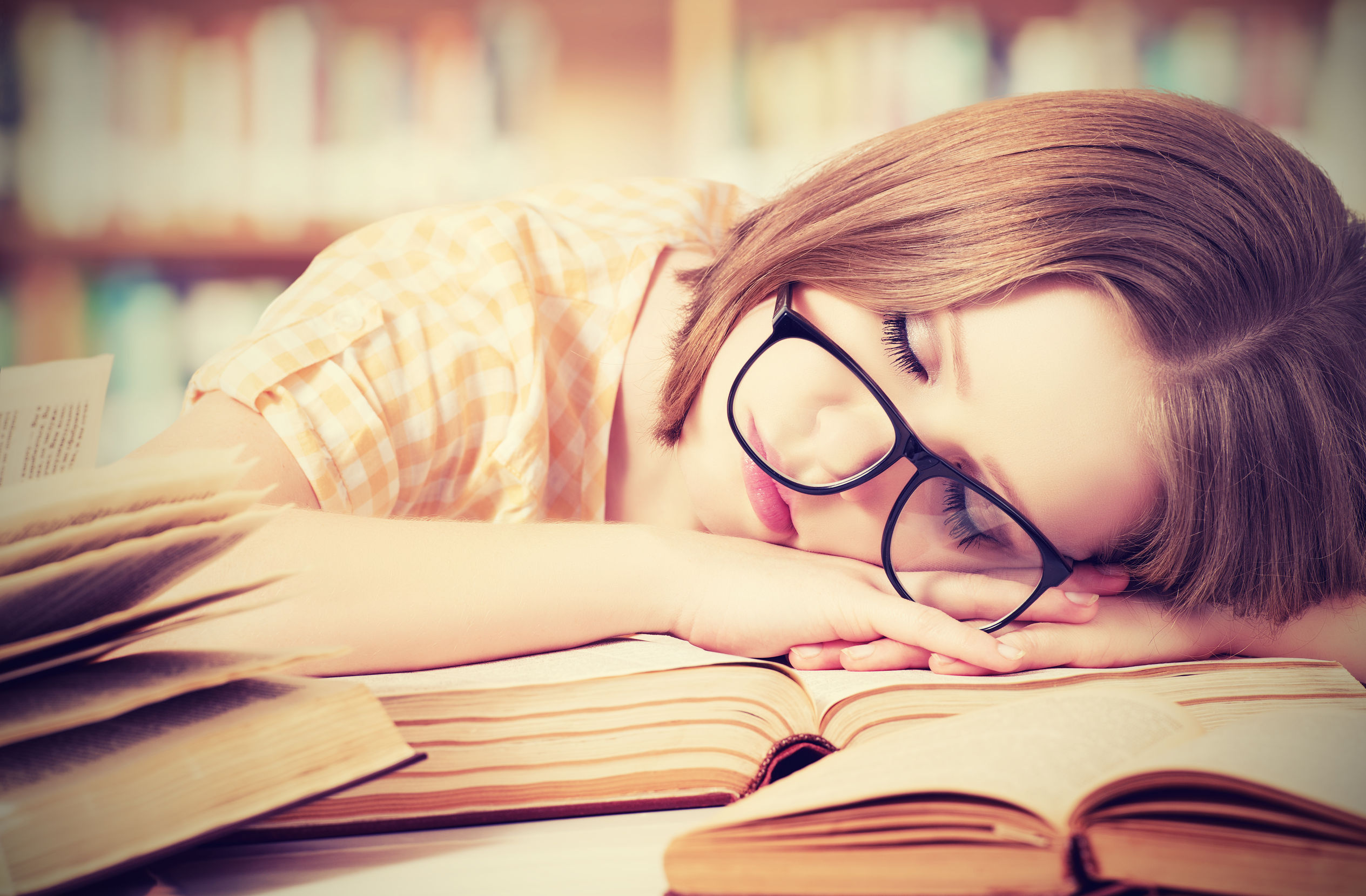 26519532 - tired student girl with glasses sleeping on the books in the library