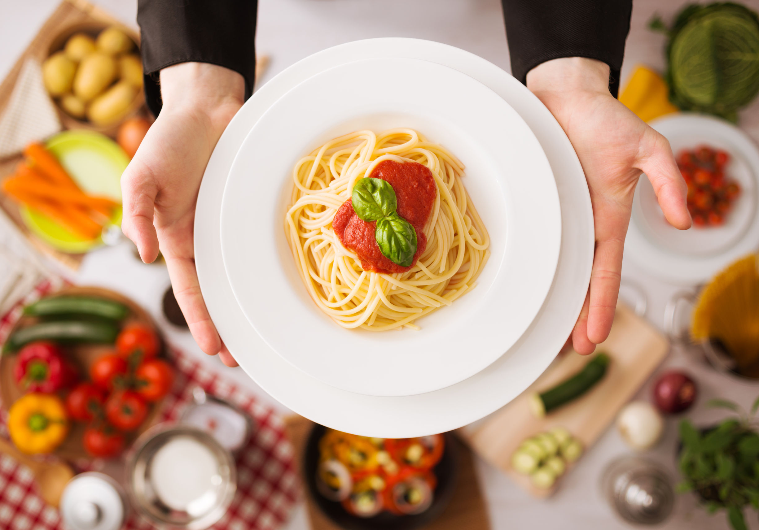 39375627 - professional chef's hands cooking pasta on a wooden worktop with vegetables, food ingredients and utensils, top view