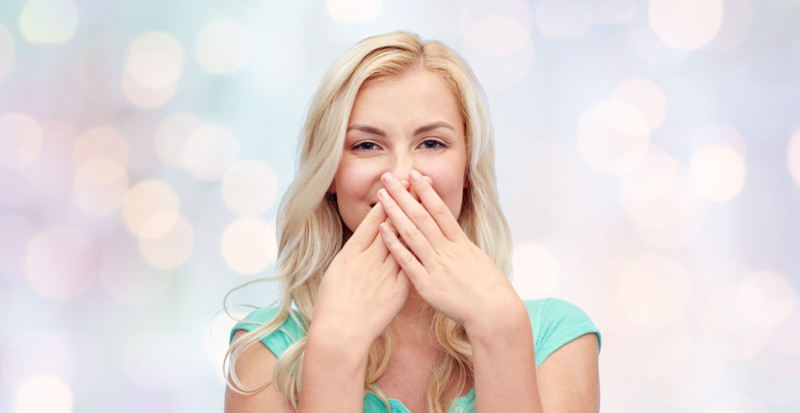 61649872 - emotions, expressions, embarrassment and people concept - confused young woman or teenage girl wrinkling and closing her nose over holidays lights background