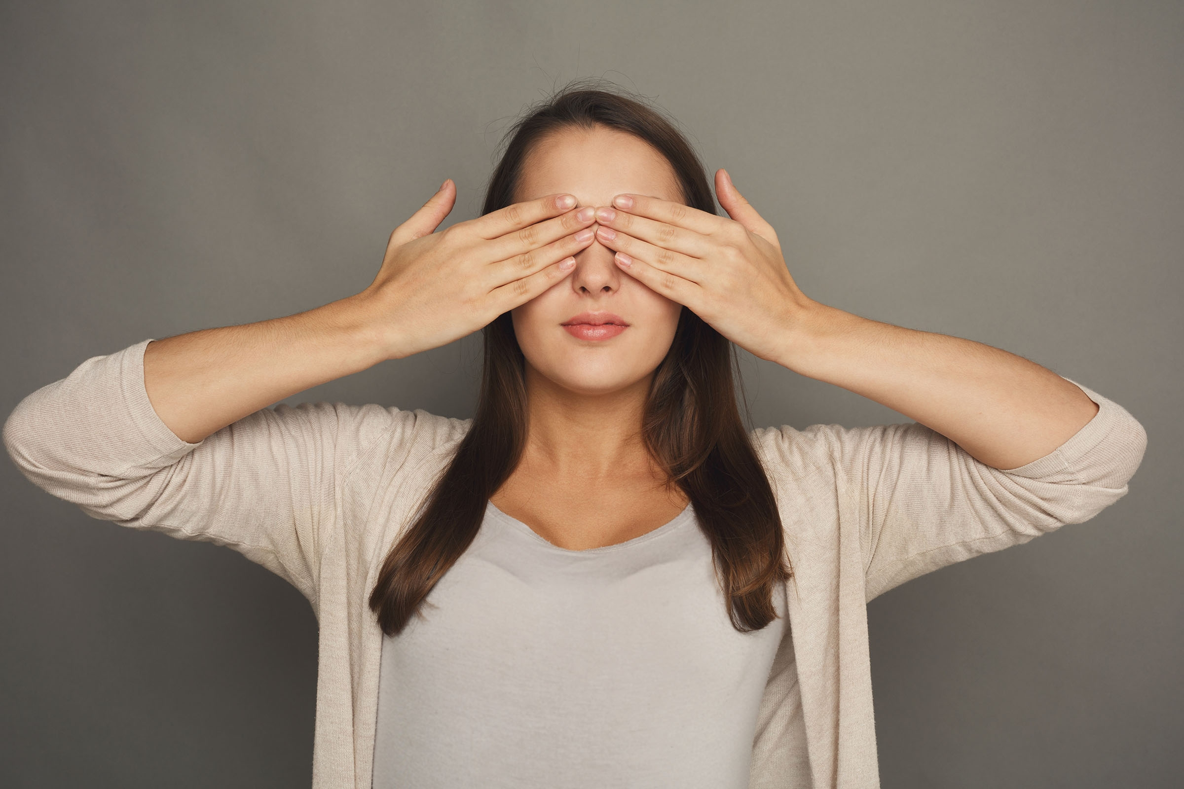 See no evil concept. Portrait of young scared woman covering eyes with hands, gray studio background.